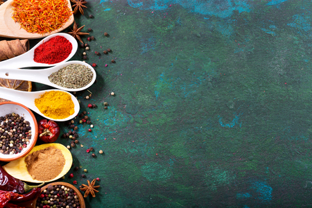 curry powder: various spices in spoons on old green background, top view