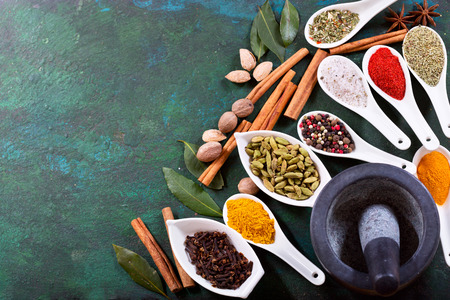 flavour: various herbs and spices for cooking on old green background, top view