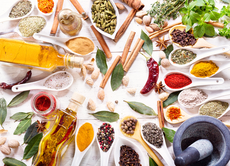 spice: various herbs, spices and vegetables for cooking on wooden table, top view