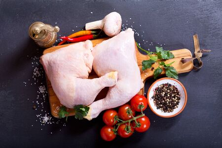 raw chicken: fresh raw chicken legs with vegetables on dark background Stock Photo