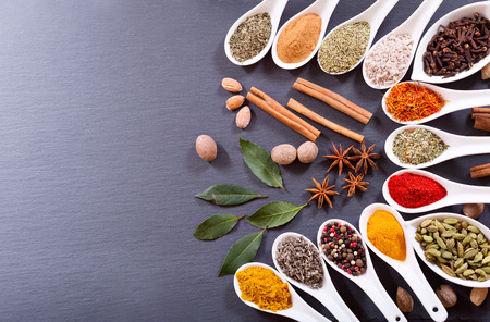 flavour: various spices in ceramic spoons on dark background, top view