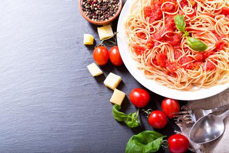 tomato sauce: plate of pasta with tomato sauce on dark background