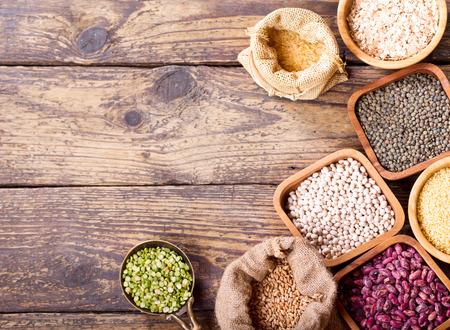 legumbres secas: cereales diferentes, semillas, frijoles y granos en la mesa de madera Foto de archivo