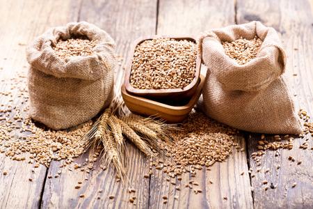 semilla: los granos de trigo en sacos de mesa de madera