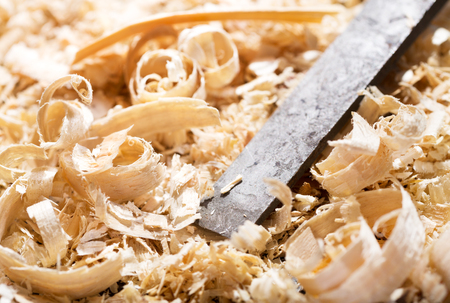 old furniture: old chisel and wood shavings in a workshop