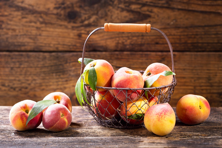 wooden basket: fresh peaches in a basket on wooden table