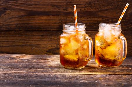 ice water: jars of peach iced tea on wooden table
