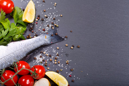 fresh fish: fresh fish with spices and vegetables on dark background Stock Photo