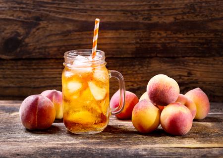 Potje van perzik ijsthee met vers fruit Stockfoto - 58134214