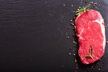 carne fresca con romero a bordo oscuro