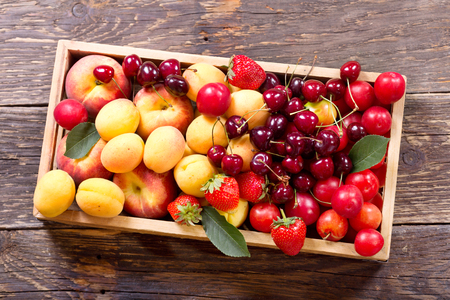 assorted: fresh fruits and berries in wooden box, top view