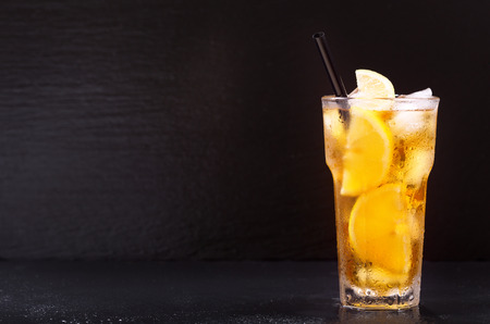 glass of lemon iced tea on dark background