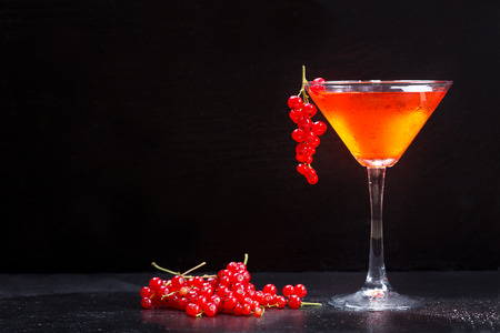 cosmopolitan: cosmopolitan cocktail with red currant on dark background