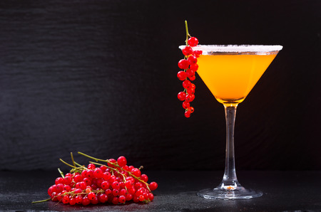red currant: orange cocktail with red currant on dark background