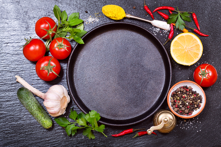 pan: various food ingredients for cooking with empty pan on dark board