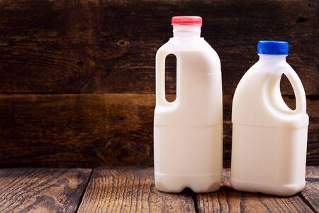 latte fresco: bottiglie di latte su sfondo in legno