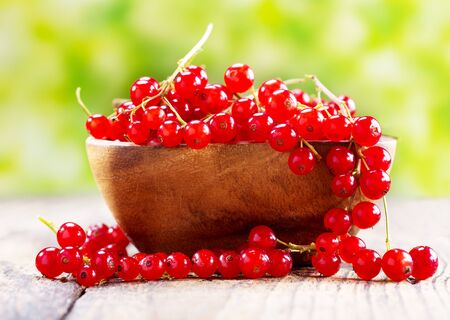red currant: fresh red currant in bowl on wooden table, over green background