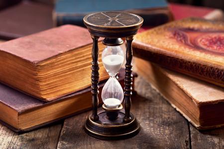 libros antiguos: antiguo reloj de arena con los libros en el fondo de madera Foto de archivo