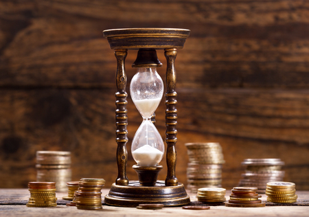 business tool: hourglass and coins on old wooden background