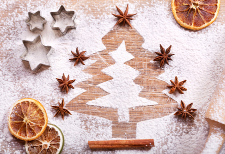 christmas cooking: Christmas cooking: fir tree made from flour on desk, ingredients for baking and dried fruits on wooden table, top view