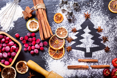 christmas cooking: Christmas cooking: fir tree made from flour on a dark table, ingredients for baking, frozen cranberry and dried fruits on dark background, top view Stock Photo