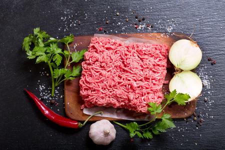 gehakt vlees met groenten op donkere bord Stockfoto