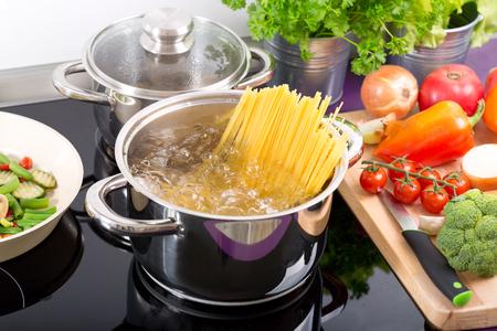 pan met kokend water met spaghetti op het fornuis in de keuken Stockfoto
