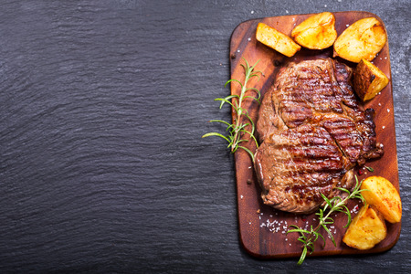 grilled meat with rosemary and vegetables on dark background Standard-Bild