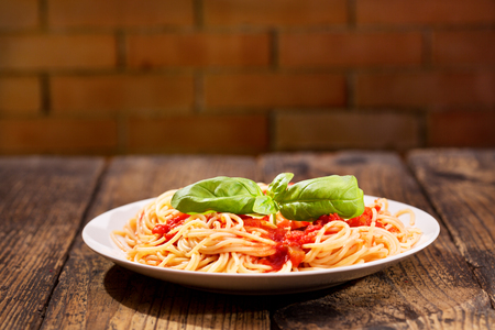 pasta sauce: plate of pasta with tomato sauce and green basil on wooden table