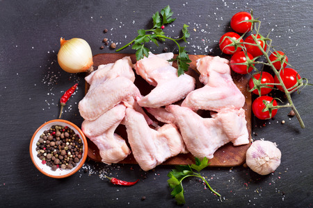 fresh raw chicken wings with vegetables on dark background, top view Stock Photo