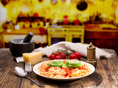 gourmet kitchen: plate of pasta with tomato sauce and green basil on wooden table in a kitchen