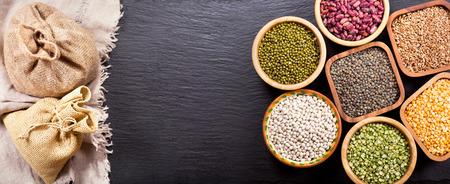 legumbres secas: cereales diferentes, semillas, frijoles y granos en fondo oscuro