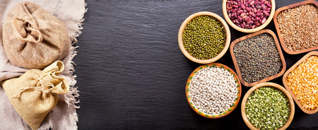 legumbres secas: various cereals, seeds, beans and grains on dark background Foto de archivo