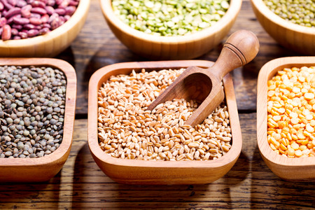 legumbres secas: various cereals, seeds, beans and grains on wooden table Foto de archivo