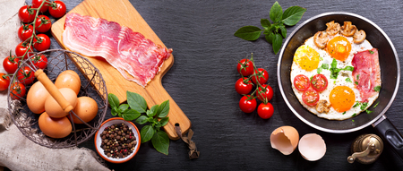 pan: breakfast with fried eggs in a pan with bacon and vegetables on dark background, top view, banner Stock Photo