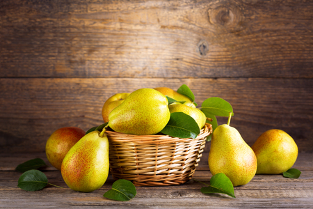 wooden basket: fresh pears with leaves in a basket on wooden background Stock Photo