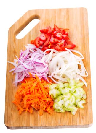 picada: Verduras frescas picadas en una tabla de cortar, aislado en fondo blanco Foto de archivo