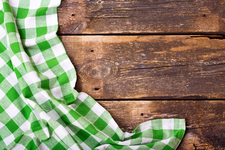 servilletas: green tablecloth on wooden table, top view