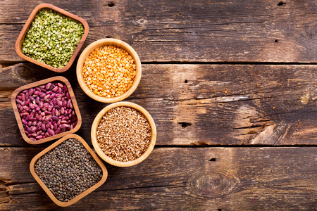 grains: various cereals, seeds, beans and grains on wooden table Stock Photo