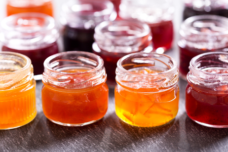 ダークウッドのテーブルにフルーツの様々 な瓶ジャムします。