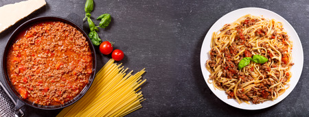 pasta sauce: plate of pasta bolognese and ingredients for cooking on dark background, top view with copy space