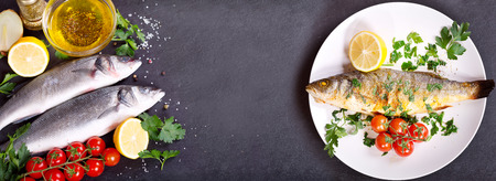 prepared dish: plate of baked sea bass and fresh fish with ingredients for cooking on dark background, top view with copy space
