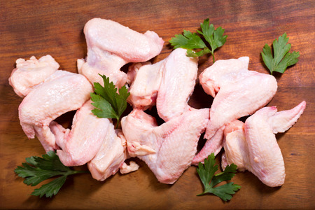 diet dinner: fresh chicken wings on wooden board, top view Stock Photo