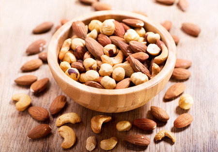 mixed nuts in a bowl on wooden table Banco de Imagens