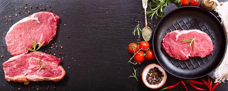 carne roja: Carne fresca con romero en una sartén en tablero oscuro, vista superior con espacio de copia Foto de archivo