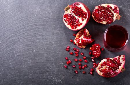 antioxidants: glass of pomegranate juice with fresh fruits on dark background, top view