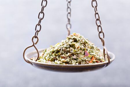 green herbs: close up of mixed dried green herbs  in a balance scale