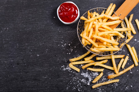 delicious food: French fries with ketchup on dark table