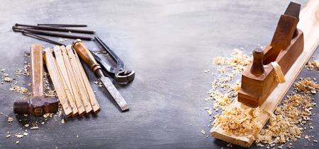 old tools: wooden planer, hammer, chisel  in a carpentry workshop on dark background, banner