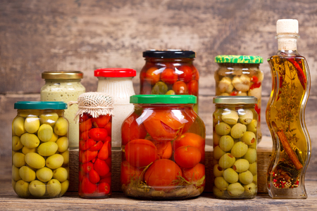 various preserved food on a wooden background Stock Photo